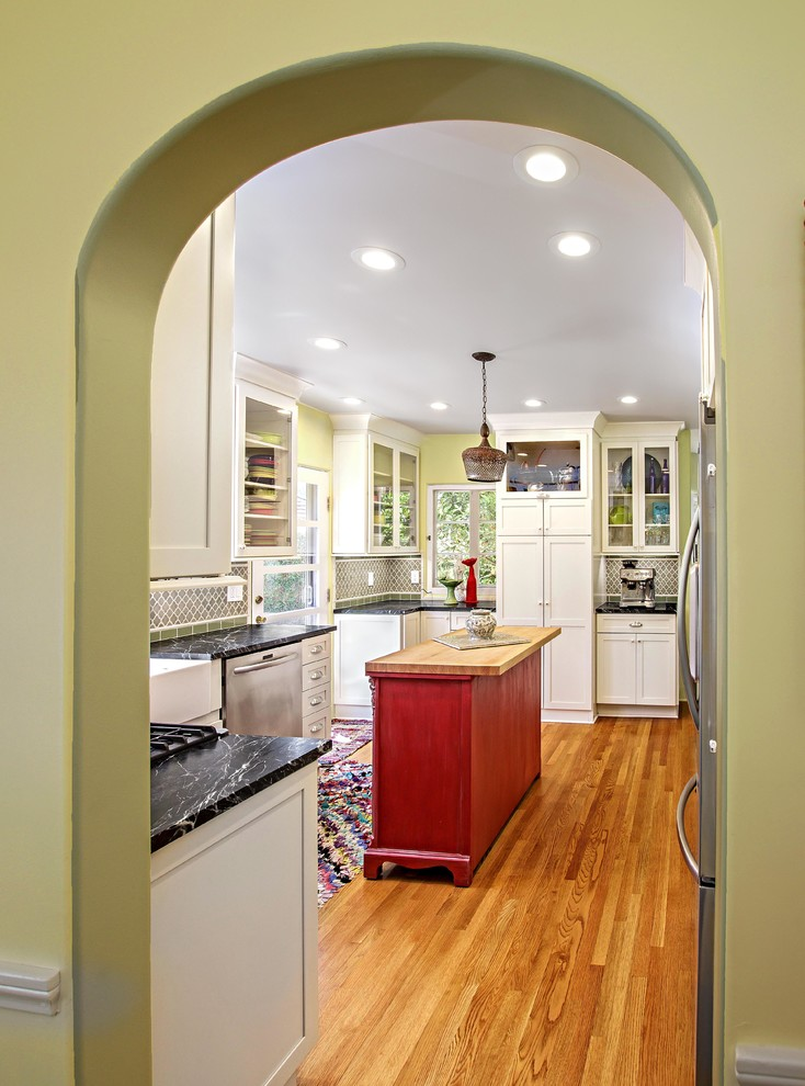 Kitchen - mid-sized eclectic l-shaped medium tone wood floor kitchen idea in Orange County with a farmhouse sink, shaker cabinets, white cabinets, soapstone countertops, green backsplash, glass tile backsplash, stainless steel appliances and an island