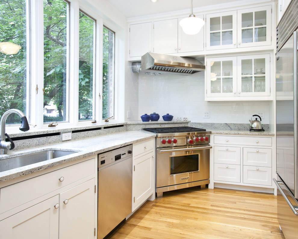 Inspiration for a contemporary kitchen remodel in New York with glass-front cabinets and stainless steel appliances