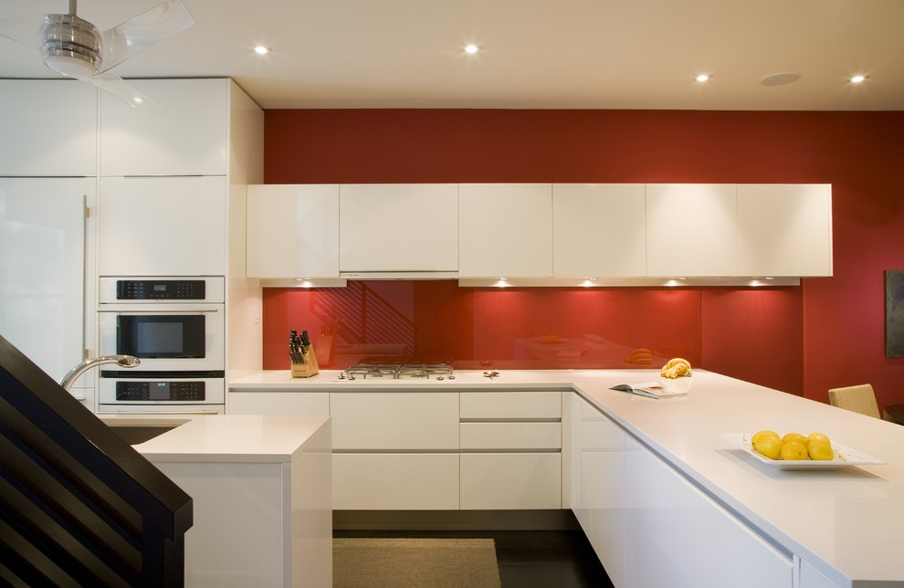 Example of a minimalist kitchen design in DC Metro with white appliances, an undermount sink, flat-panel cabinets, white cabinets, red backsplash and glass sheet backsplash