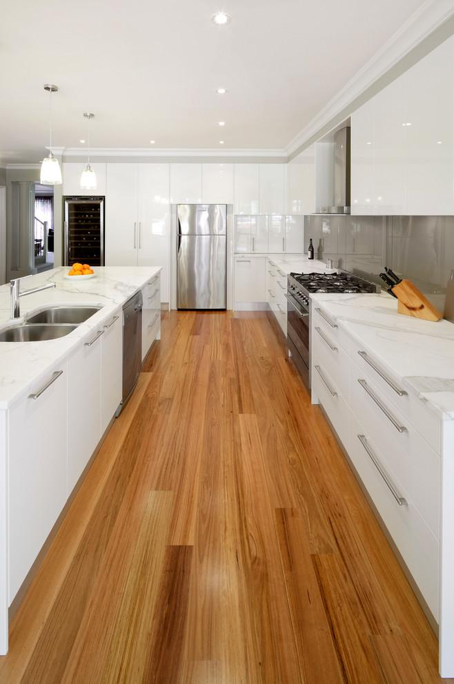 Kitchen - mid-sized modern l-shaped light wood floor kitchen idea in Sydney with an undermount sink, white cabinets, marble countertops, metallic backsplash, glass sheet backsplash, stainless steel appliances and an island