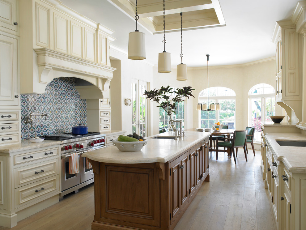 Inspiration for a large mediterranean galley light wood floor and beige floor eat-in kitchen remodel in Miami with an undermount sink, raised-panel cabinets, beige cabinets, multicolored backsplash, stainless steel appliances, an island, granite countertops and mosaic tile backsplash