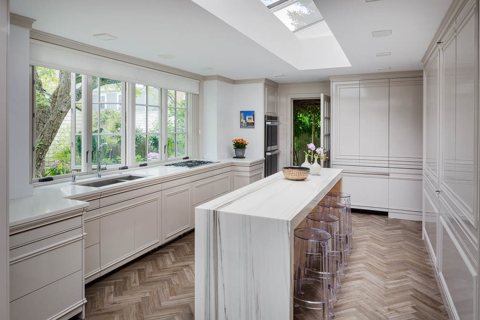Example of a large trendy u-shaped medium tone wood floor enclosed kitchen design in Boston with an undermount sink, flat-panel cabinets, white cabinets, quartz countertops, white backsplash, white appliances and an island
