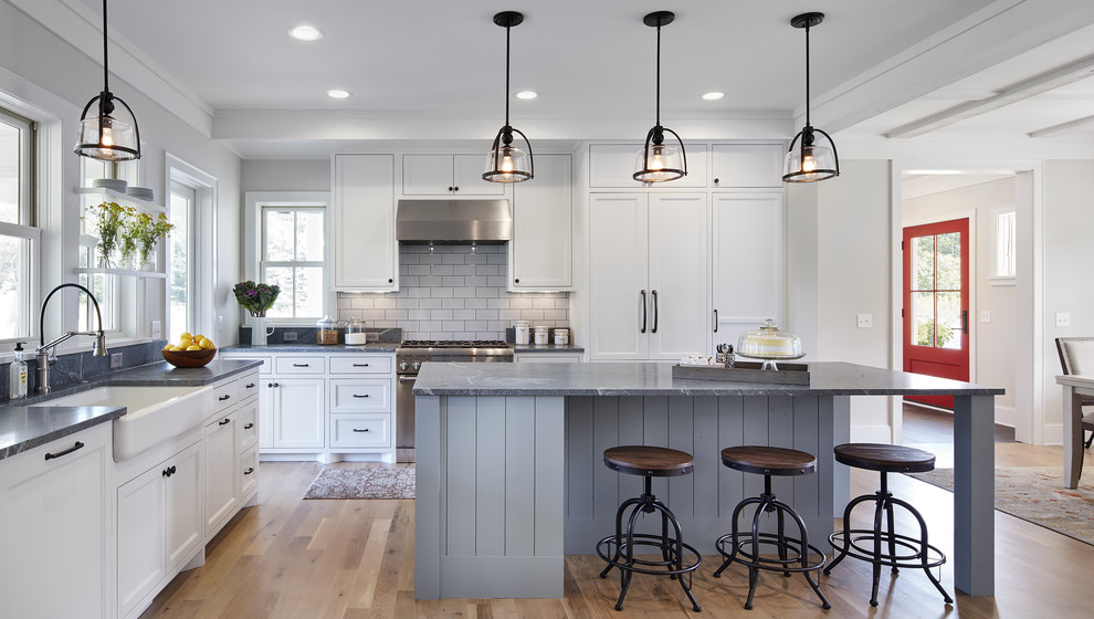 Eat-in kitchen - mid-sized cottage l-shaped light wood floor and brown floor eat-in kitchen idea in Minneapolis with a farmhouse sink, white cabinets, soapstone countertops, white backsplash, an island, stone tile backsplash, paneled appliances and recessed-panel cabinets
