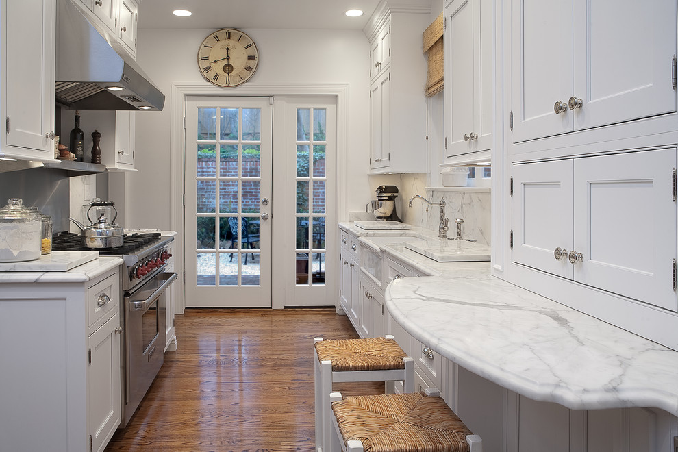 Enclosed kitchen - traditional galley light wood floor enclosed kitchen idea in DC Metro with a farmhouse sink, beaded inset cabinets, white cabinets, stainless steel appliances, stone slab backsplash, white backsplash, marble countertops and no island