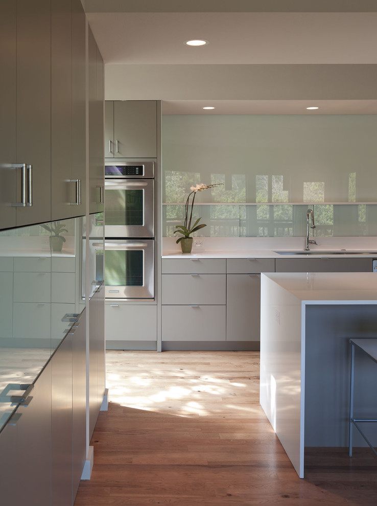 Example of a mid-sized minimalist galley medium tone wood floor and brown floor eat-in kitchen design in Austin with stainless steel appliances, flat-panel cabinets, gray cabinets, quartz countertops, glass sheet backsplash, an undermount sink and an island