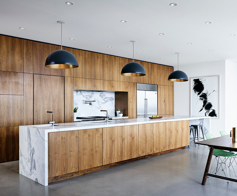 Minimalist galley concrete floor and gray floor open concept kitchen photo in Austin with an undermount sink, flat-panel cabinets, medium tone wood cabinets, marble countertops, white backsplash, stone slab backsplash, stainless steel appliances and an island