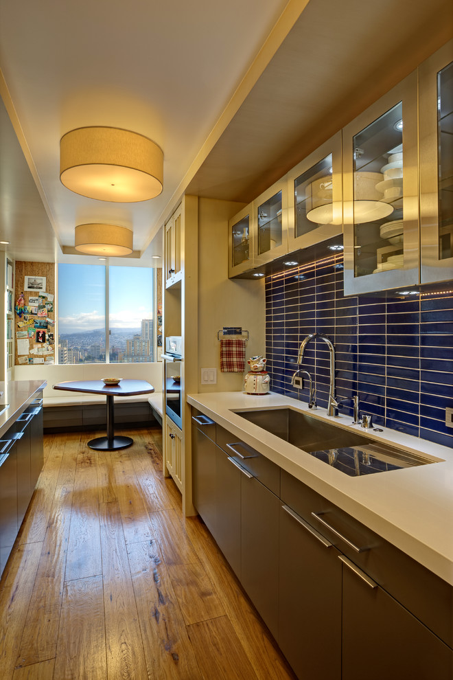 Eat-in kitchen - small contemporary galley medium tone wood floor and yellow floor eat-in kitchen idea in San Francisco with an undermount sink, glass-front cabinets, stainless steel cabinets, solid surface countertops, blue backsplash, ceramic backsplash, stainless steel appliances and a peninsula