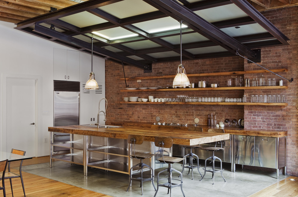 Inspiration for a mid-sized industrial l-shaped concrete floor and gray floor eat-in kitchen remodel in New York with stainless steel appliances, stainless steel cabinets, wood countertops, flat-panel cabinets, red backsplash, brick backsplash, an island and a farmhouse sink