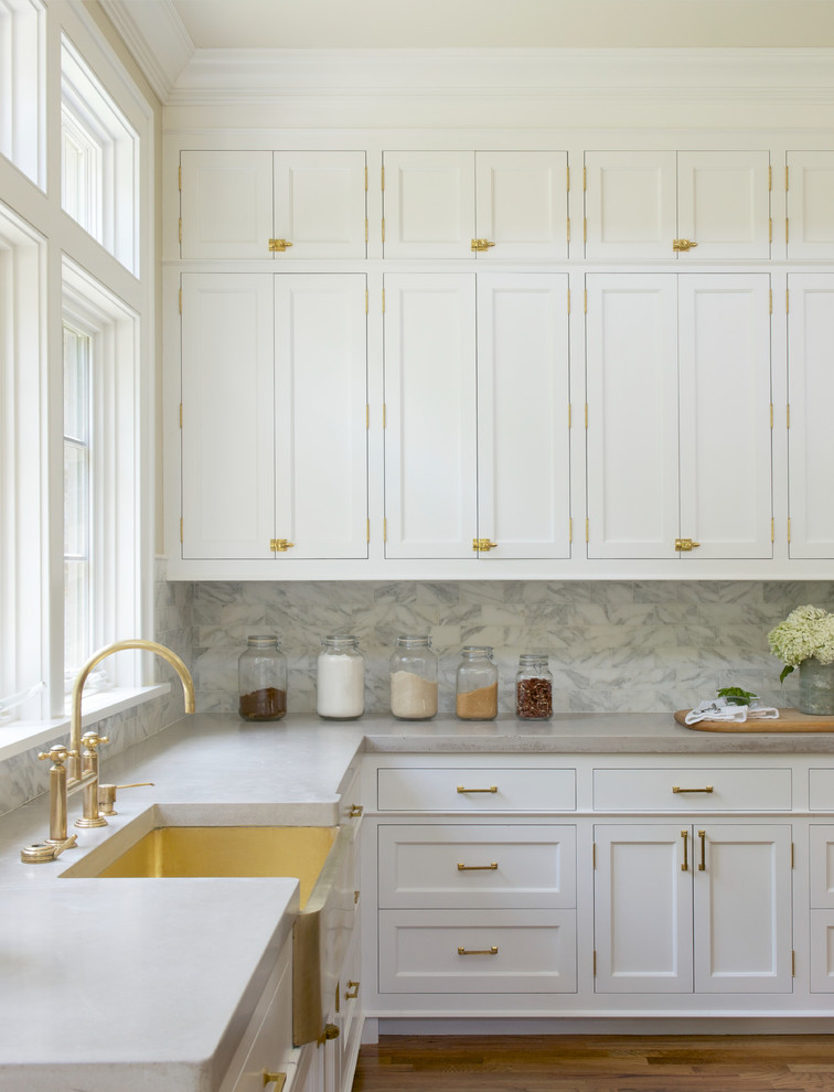 Inspiration for a transitional u-shaped medium tone wood floor open concept kitchen remodel in New York with a farmhouse sink, shaker cabinets, white cabinets, white backsplash, marble countertops, an island and marble backsplash