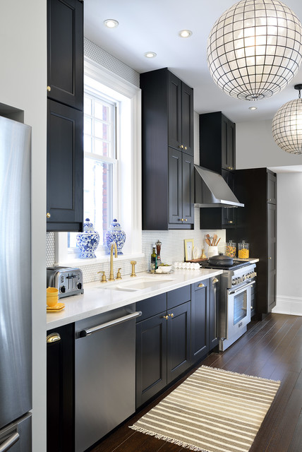 Inspiration for a mid-sized transitional galley dark wood floor kitchen remodel in Toronto with a double-bowl sink, recessed-panel cabinets, black cabinets, quartz countertops, white backsplash, stainless steel appliances and mosaic tile backsplash