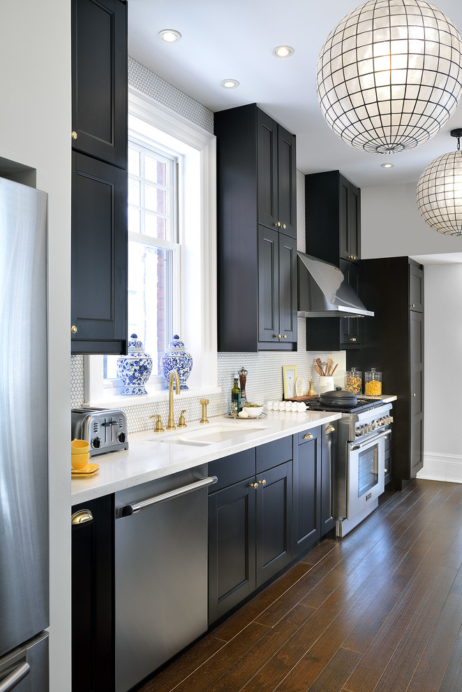 Inspiration for a timeless single-wall dark wood floor enclosed kitchen remodel in Toronto with black cabinets, quartzite countertops, white backsplash, mosaic tile backsplash, stainless steel appliances, a double-bowl sink and shaker cabinets