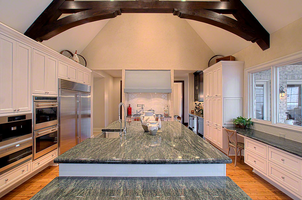 Inspiration for a large timeless u-shaped light wood floor and brown floor eat-in kitchen remodel in Chicago with a farmhouse sink, recessed-panel cabinets, white cabinets, granite countertops, white backsplash, ceramic backsplash, stainless steel appliances and an island