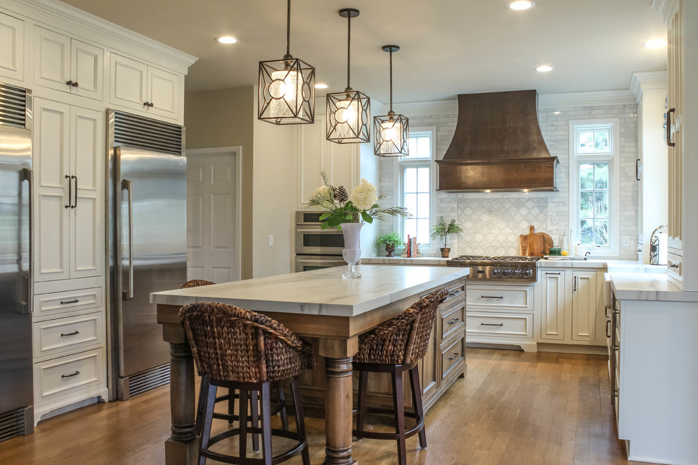 Large tuscan medium tone wood floor and brown floor kitchen photo in Detroit with a farmhouse sink, white cabinets, quartz countertops, white backsplash, marble backsplash, stainless steel appliances, an island, white countertops and recessed-panel cabinets