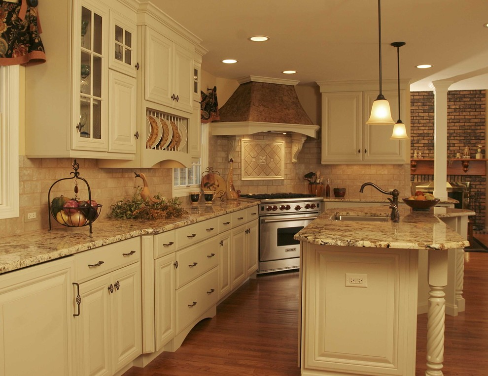 Large french country l-shaped medium tone wood floor eat-in kitchen photo in Chicago with a double-bowl sink, raised-panel cabinets, white cabinets, granite countertops, beige backsplash, stainless steel appliances and an island