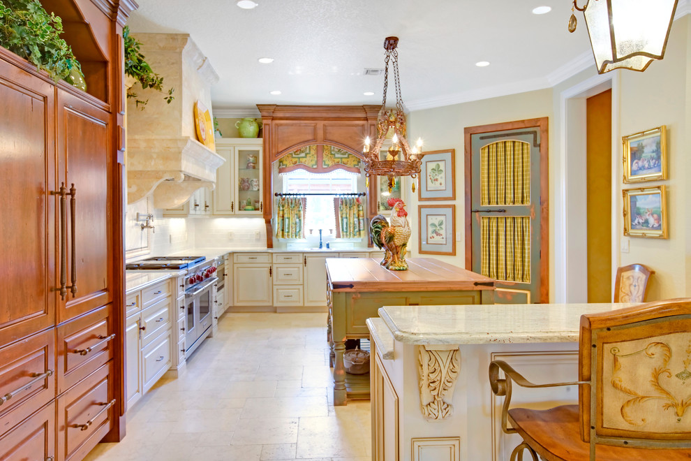 Example of a tuscan kitchen design in Orlando with paneled appliances