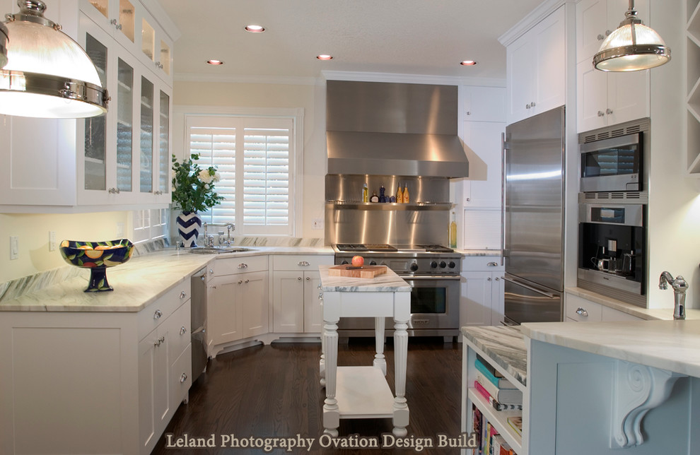 Mid-sized elegant u-shaped dark wood floor and brown floor kitchen photo in Portland with shaker cabinets, white cabinets, marble countertops, stainless steel appliances and an island