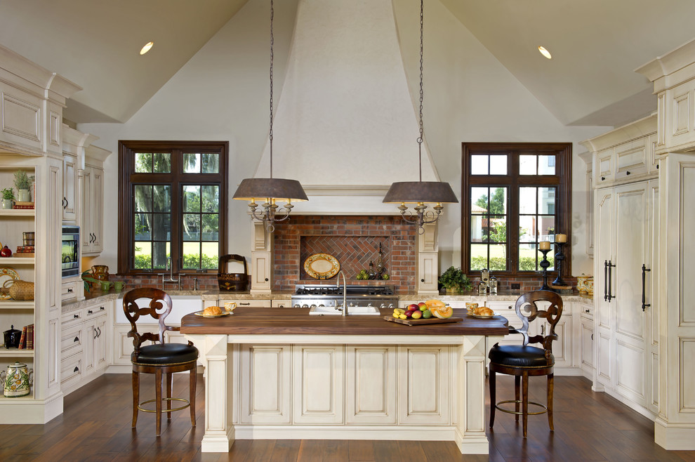 Inspiration for a timeless u-shaped kitchen remodel in Orlando with raised-panel cabinets, beige cabinets and paneled appliances