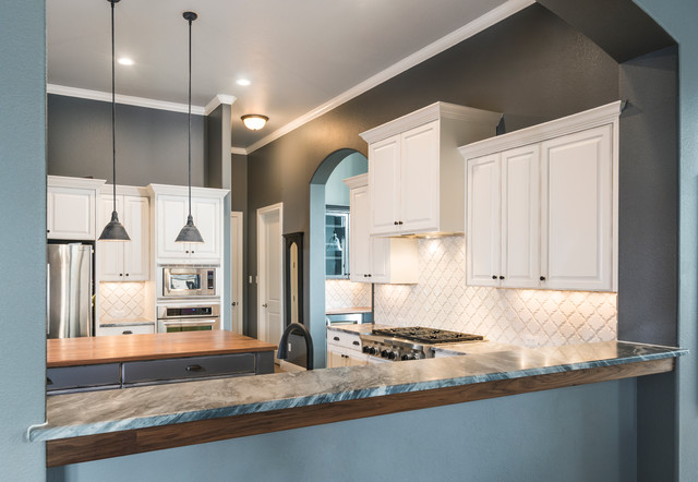 Large cottage u-shaped ceramic floor open concept kitchen photo in Austin with a farmhouse sink, raised-panel cabinets, distressed cabinets, marble countertops, white backsplash, ceramic backsplash, stainless steel appliances and an island