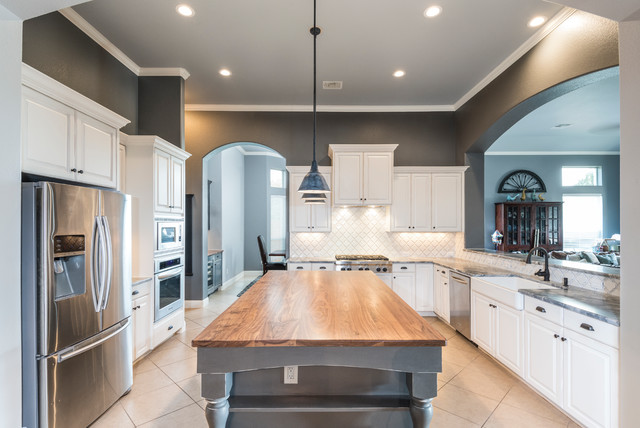 Large country u-shaped ceramic floor open concept kitchen photo in Austin with a farmhouse sink, raised-panel cabinets, distressed cabinets, marble countertops, white backsplash, ceramic backsplash, stainless steel appliances and an island