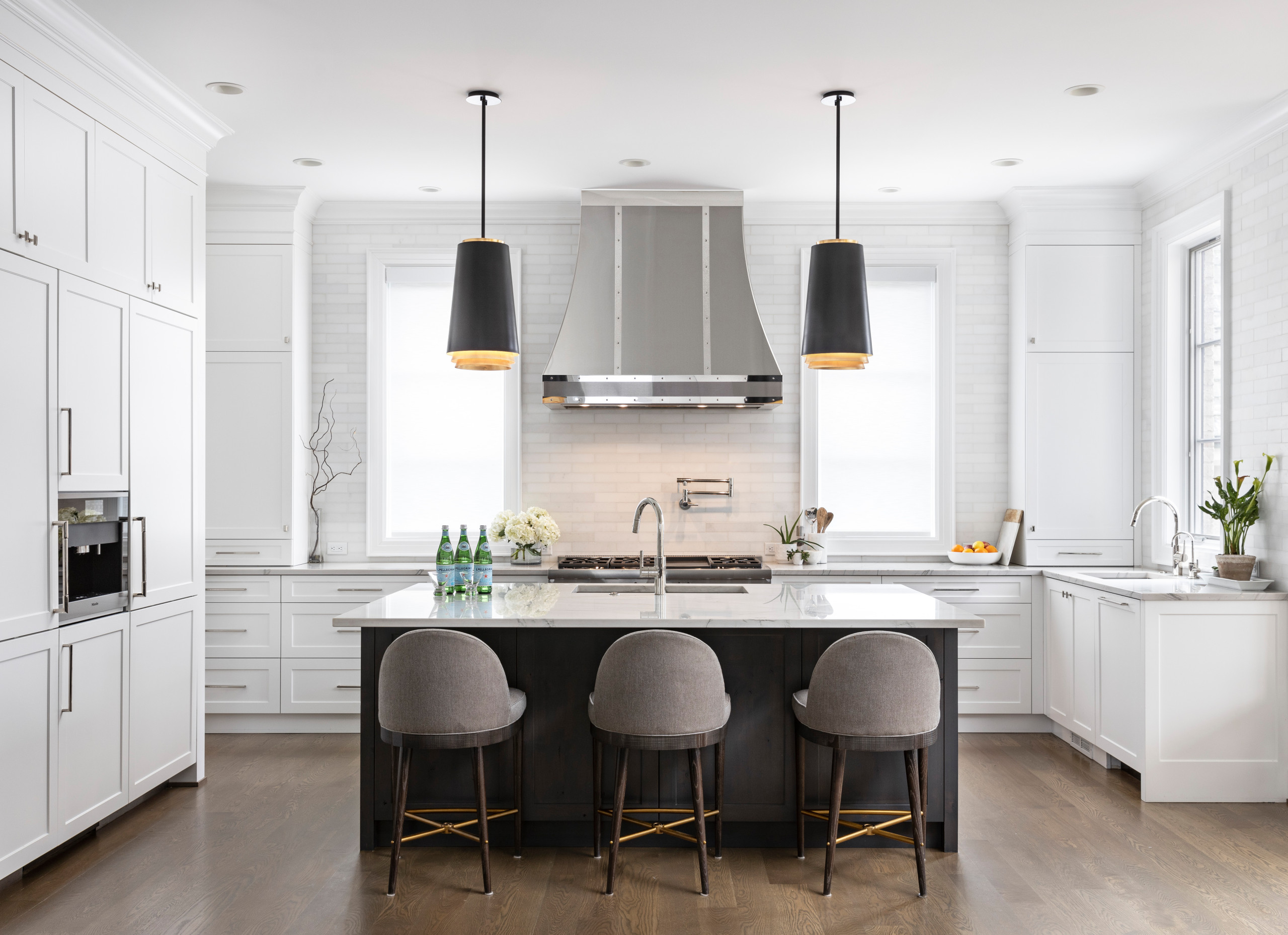 Serenity in the Kitchen. When working with an open floor plan, it's essential to tie in these spaces with the rest of the Home. The custom metal hood becomes the star of the show, and you can be sure