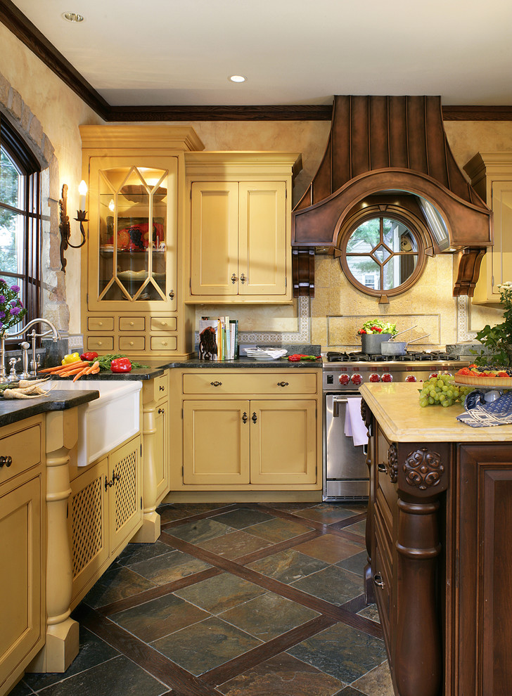 Example of a large french country l-shaped slate floor and brown floor eat-in kitchen design in New York with beaded inset cabinets, a farmhouse sink, yellow cabinets, soapstone countertops, yellow backsplash, stainless steel appliances, mosaic tile backsplash and an island