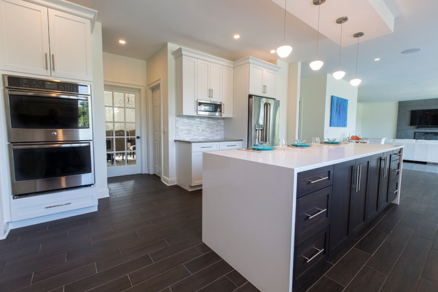 Inspiration for a huge contemporary l-shaped porcelain floor open concept kitchen remodel in Bridgeport with an undermount sink, shaker cabinets, white cabinets, quartz countertops, white backsplash, mosaic tile backsplash, stainless steel appliances and an island