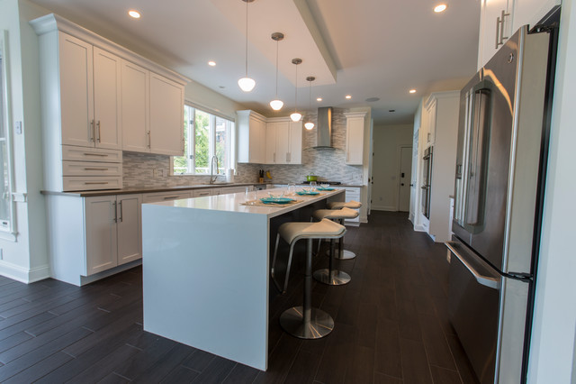 Example of a huge trendy l-shaped porcelain floor open concept kitchen design in Bridgeport with an undermount sink, shaker cabinets, white cabinets, quartz countertops, white backsplash, mosaic tile backsplash, stainless steel appliances and an island