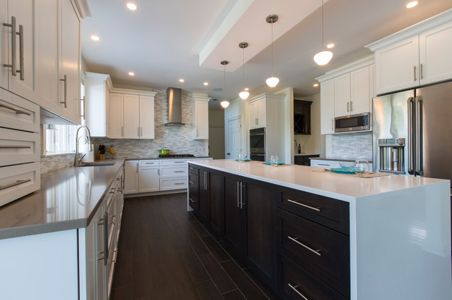 Huge trendy l-shaped porcelain floor open concept kitchen photo in Bridgeport with an undermount sink, shaker cabinets, white cabinets, quartz countertops, white backsplash, mosaic tile backsplash, stainless steel appliances and an island