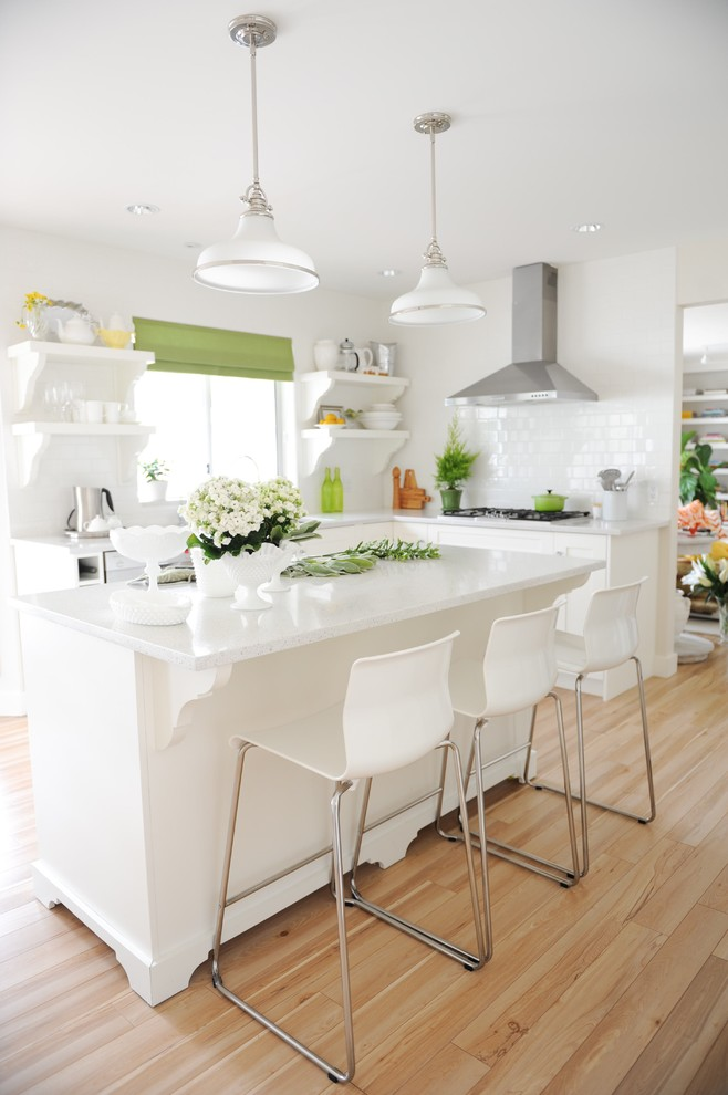 Mid-sized transitional l-shaped laminate floor enclosed kitchen photo in Vancouver with an undermount sink, open cabinets, white cabinets, quartz countertops, white backsplash, ceramic backsplash and stainless steel appliances