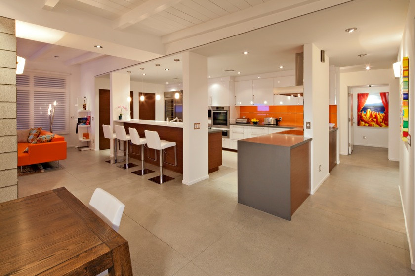 Example of a large trendy u-shaped concrete floor open concept kitchen design in Los Angeles with flat-panel cabinets, white cabinets, stainless steel appliances, an island and orange backsplash