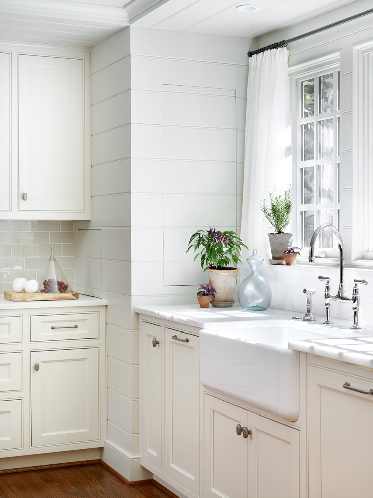 Inspiration for a mid-sized transitional u-shaped medium tone wood floor and brown floor enclosed kitchen remodel in Atlanta with a farmhouse sink, beaded inset cabinets, white cabinets, an island, gray backsplash, subway tile backsplash, stainless steel appliances and marble countertops