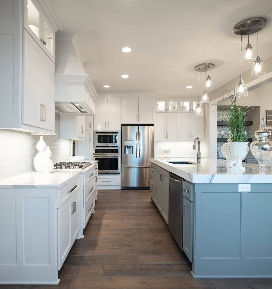 Open concept kitchen - craftsman l-shaped medium tone wood floor and brown floor open concept kitchen idea in Kansas City with a drop-in sink, white cabinets, white backsplash, stainless steel appliances, an island and white countertops