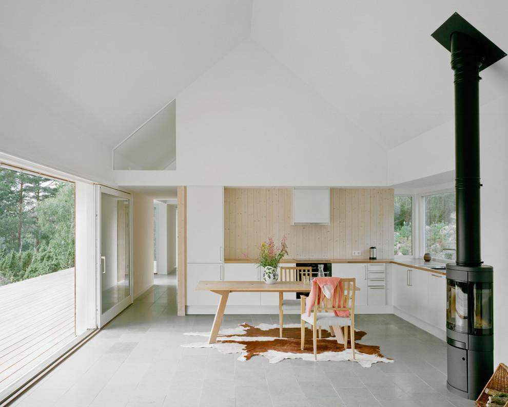 Nordisk inredning av ett stort kök, med släta luckor, vita skåp, integrerade vitvaror, en nedsänkt diskho, träbänkskiva och klinkergolv i keramik