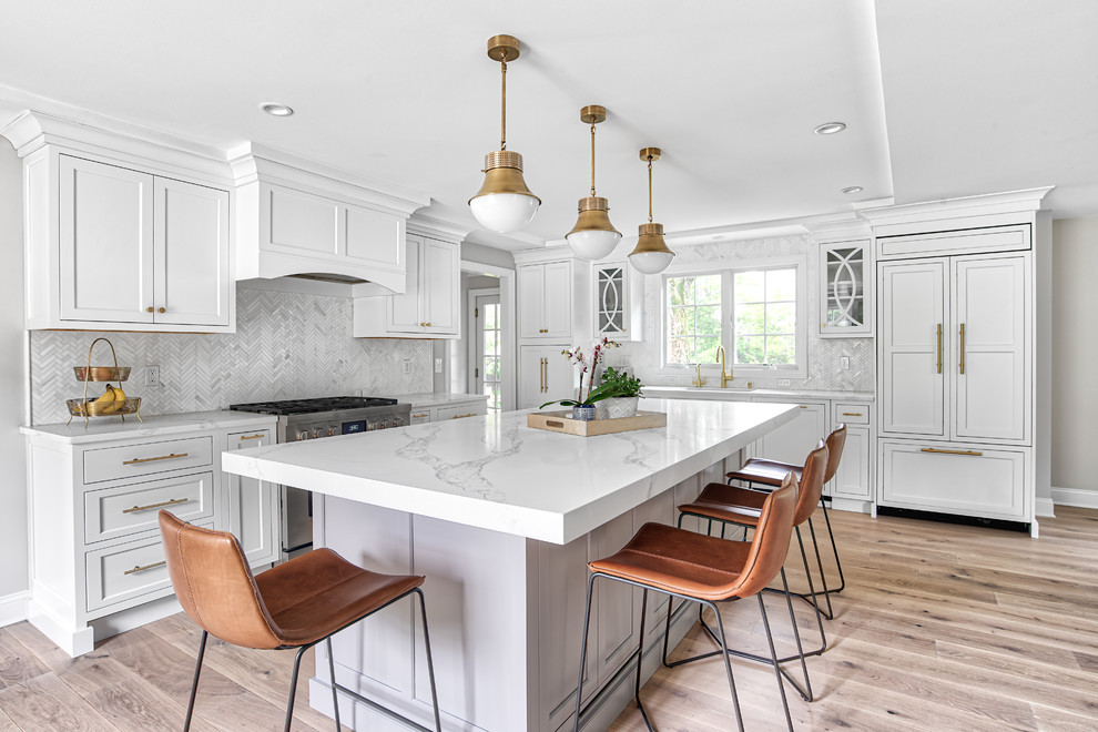 Inspiration for a large transitional l-shaped light wood floor and beige floor eat-in kitchen remodel in New York with paneled appliances, an island, an undermount sink, white cabinets, quartz countertops, white backsplash, mosaic tile backsplash, white countertops and shaker cabinets