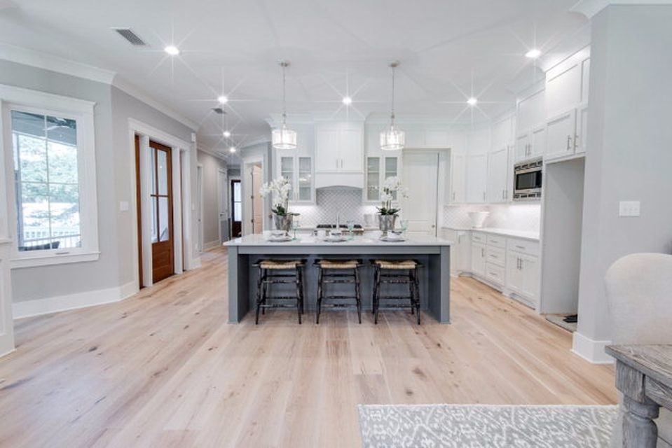 Eat-in kitchen - large craftsman galley light wood floor eat-in kitchen idea in Other with a farmhouse sink, flat-panel cabinets, white cabinets, granite countertops, white backsplash, mosaic tile backsplash, stainless steel appliances and an island