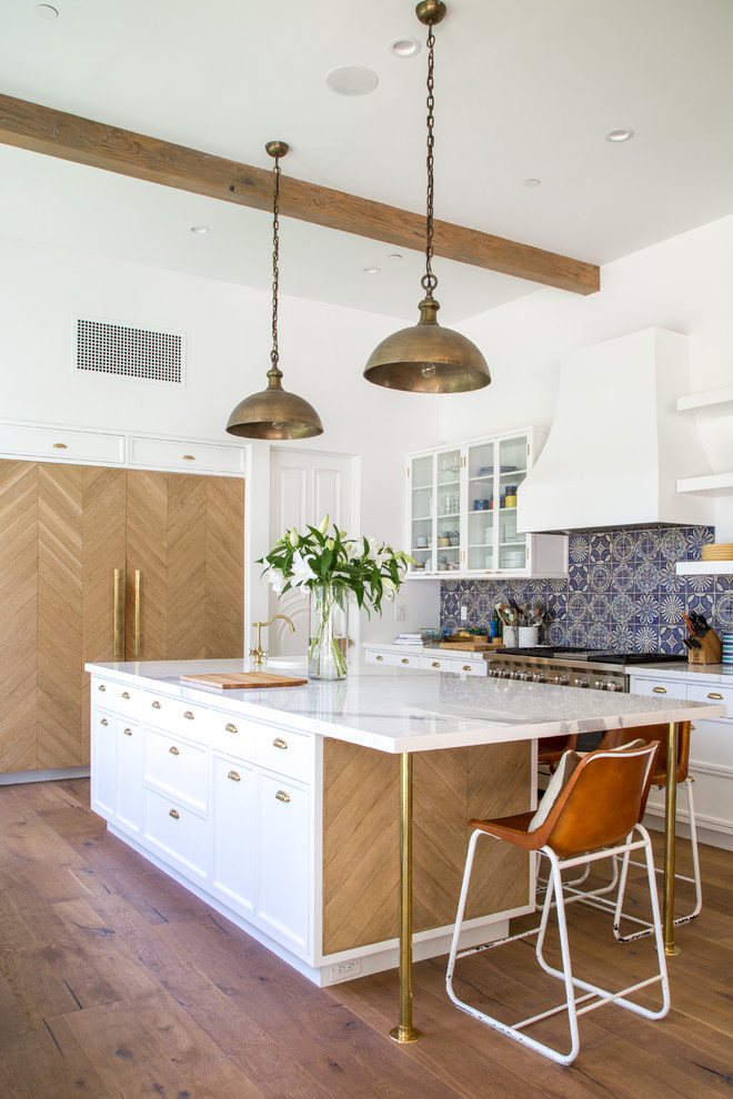 Inspiration for a large transitional single-wall light wood floor and brown floor open concept kitchen remodel in Los Angeles with a farmhouse sink, recessed-panel cabinets, white cabinets, marble countertops, gray backsplash, ceramic backsplash, paneled appliances and an island
