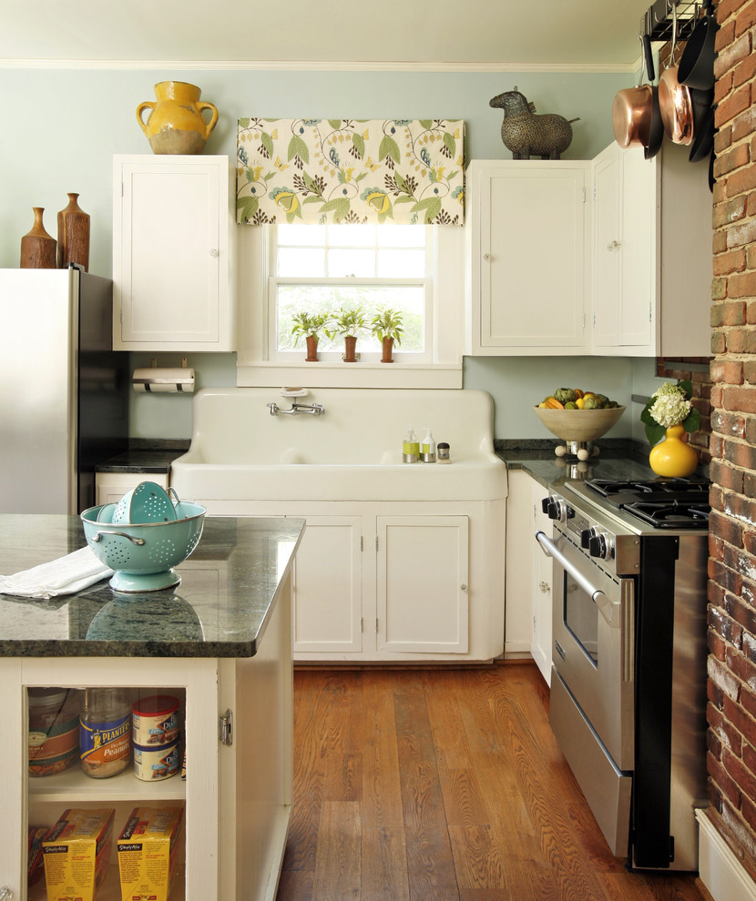 Inspiration for a mid-sized eclectic l-shaped medium tone wood floor kitchen remodel in Dallas with a farmhouse sink, recessed-panel cabinets, white cabinets, granite countertops, stainless steel appliances, black backsplash and an island