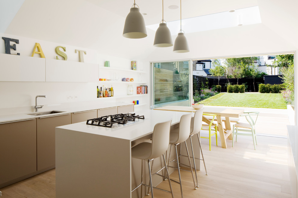 Inspiration for a mid-sized contemporary l-shaped light wood floor and beige floor eat-in kitchen remodel in London with flat-panel cabinets, solid surface countertops, white backsplash, an island, an undermount sink, beige cabinets, glass sheet backsplash, stainless steel appliances and beige countertops