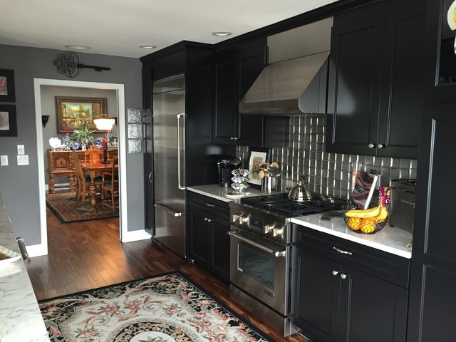 Eat-in kitchen - small transitional galley medium tone wood floor and brown floor eat-in kitchen idea in Seattle with recessed-panel cabinets, black cabinets, marble countertops, metallic backsplash, metal backsplash, stainless steel appliances, no island and an undermount sink