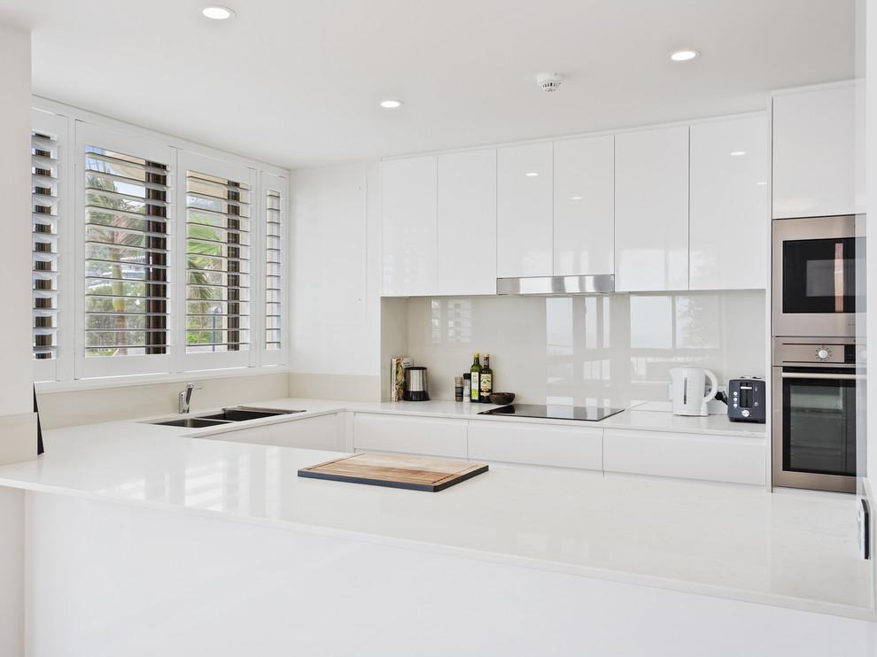 Diseño de cocina minimalista, pequeña, sin isla, con fregadero bajoencimera, armarios con paneles lisos, puertas de armario blancas, encimera de cuarzo compacto, salpicadero beige, salpicadero de vidrio templado, electrodomésticos de acero inoxidable y encimeras blancas