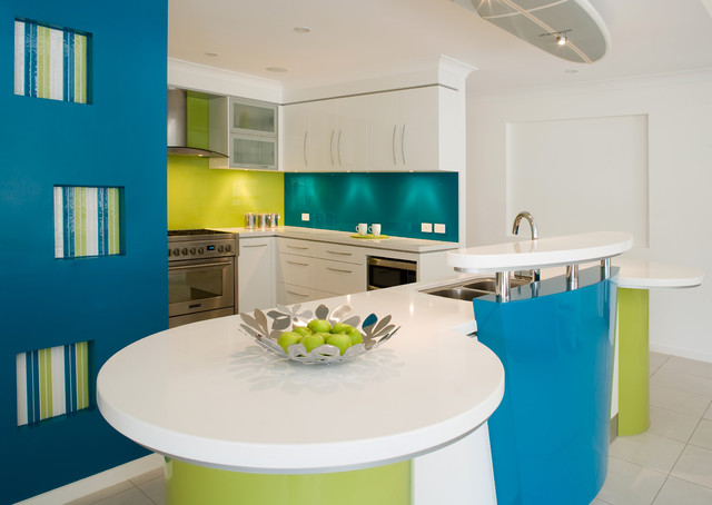 This is an example of a contemporary kitchen in Brisbane with a double-bowl sink, flat-panel cabinets, white cabinets, green splashback, glass sheet splashback and stainless steel appliances.