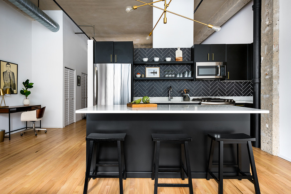 Kitchen - industrial light wood floor kitchen idea in Chicago with flat-panel cabinets, black cabinets, black backsplash, stainless steel appliances, an island and white countertops