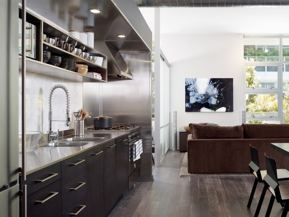 Urban single-wall brown floor open concept kitchen photo in Los Angeles with stainless steel appliances, stainless steel countertops, an integrated sink, open cabinets, white backsplash, stone slab backsplash and stainless steel cabinets