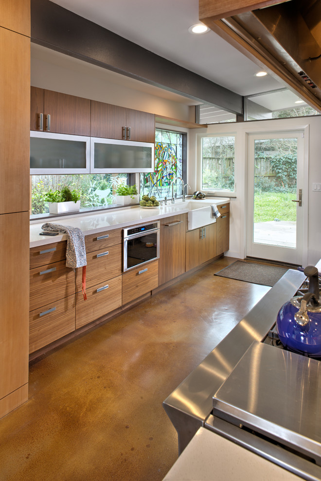 Inspiration for a mid-sized modern galley concrete floor eat-in kitchen remodel in Sacramento with a farmhouse sink, glass-front cabinets, medium tone wood cabinets, quartz countertops, stainless steel appliances and an island