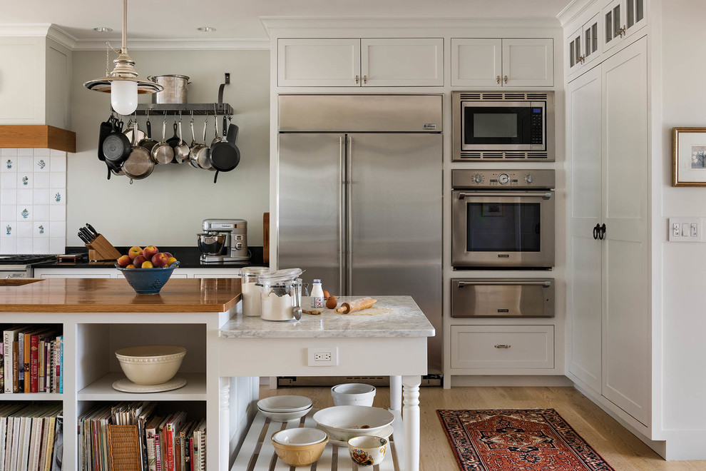 Inspiration for a mid-sized farmhouse u-shaped light wood floor and beige floor open concept kitchen remodel in Bridgeport with a farmhouse sink, shaker cabinets, white cabinets, granite countertops, white backsplash, porcelain backsplash, stainless steel appliances and an island