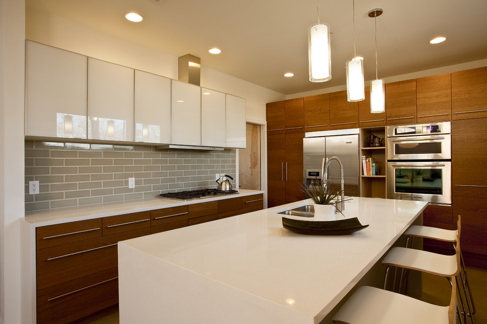 Mid-sized trendy u-shaped open concept kitchen photo in Austin with subway tile backsplash, stainless steel appliances, flat-panel cabinets, white cabinets, gray backsplash, a double-bowl sink, solid surface countertops and an island
