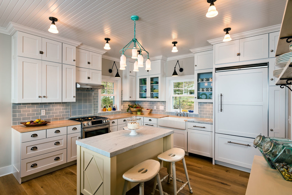 Kitchen - mid-sized country l-shaped medium tone wood floor and brown floor kitchen idea in Milwaukee with a farmhouse sink, shaker cabinets, white cabinets, wood countertops, blue backsplash, subway tile backsplash, paneled appliances and an island