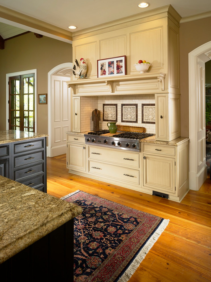 Kitchen - traditional kitchen idea in Atlanta with raised-panel cabinets, beige cabinets, beige backsplash, subway tile backsplash and stainless steel appliances