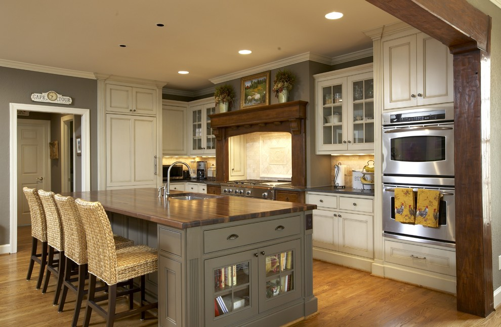 Kitchen - traditional kitchen idea in Birmingham with beaded inset cabinets, paneled appliances, wood countertops, beige cabinets and brown countertops