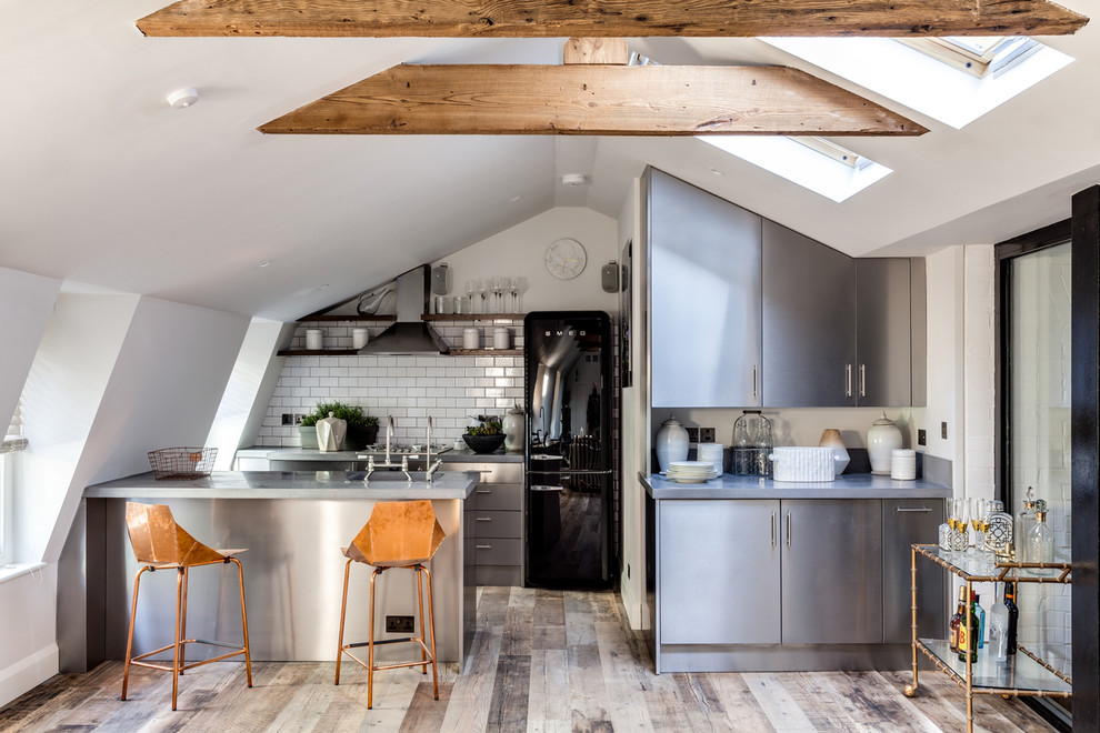 Inspiration for a small industrial galley kitchen remodel in London with flat-panel cabinets, stainless steel cabinets, white backsplash, subway tile backsplash, black appliances and a peninsula